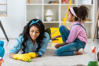 Attractive african american woman in yellow rubber gloves lying on carpet while daughter sitting near stock vector