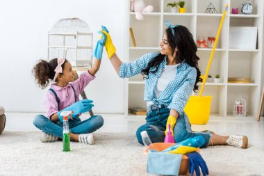 smiling african american mother and daughter holding raised hands in bright rubber gloves