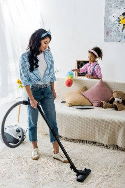attractive african american woman cleaning carpet with vacuum cleaner while cute daughter dusting sofa