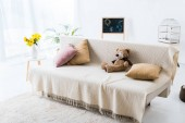 Photo light spacious room with comfortable sofa with pillows and teddy bear