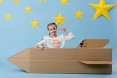 Fotografie Rozkošný chlapec s lepenkové rakety ukazovat znamení míru na modré hvězdné pozadí