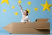 Gyerek karton rakéta mutató ujjával a csillagos-kék csillagos háttér