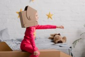 Side view of child in cardboard helmet holding hand up