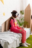 Fotografie Kid im Vr Kopfhörer sitzt auf Bett und hält digital-Tablette