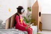 Kluk v vr headset sedí na posteli a používání digitálních tabletu