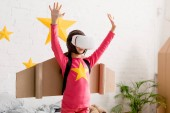 Child in vr headset standing with hands up in bedroom