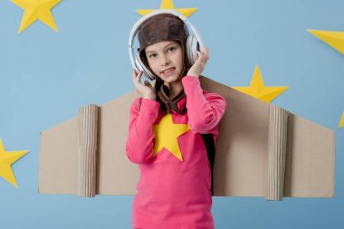 Smiling kid in white headphones looking at camera on blue background with stars