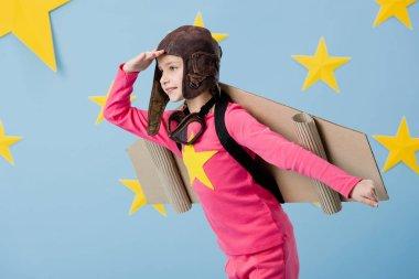 Cute child in flight helmet posing on blue starry background stock vector