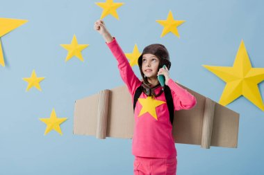 Funny kid with cardboard wings talking on smartphone on blue background with stars