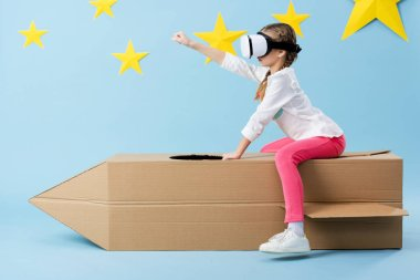 Kid in vr headset sitting on cardboard rocket and holding fist up on blue background with stars stock vector