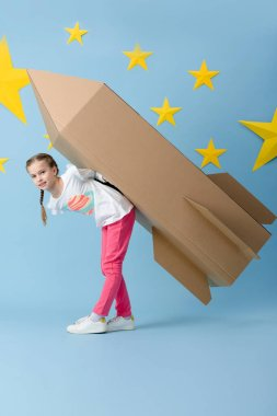 Cute kid in pink pants holding big cardboard rocket on blue starry background stock vector