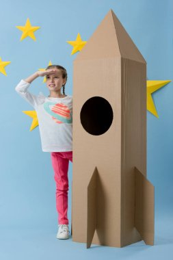Cheerful kid standing near cardboard rocket and looking away on blue starry background stock vector