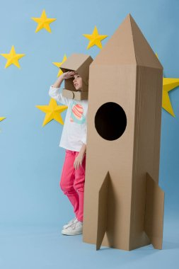 Kid in cardboard helmet standing near rocket and looking away on blue starry background stock vector
