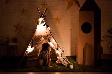 Kid standing on all fours in wigwam and looking at cardboard rocket in dark room