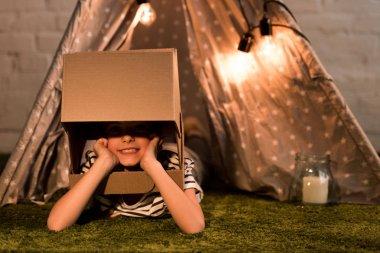 Funny kid in cardboard helmet lying on green carpet