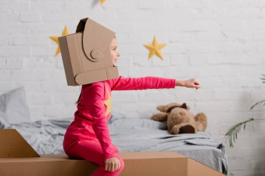 Side view of child in cardboard helmet holding hand up stock vector
