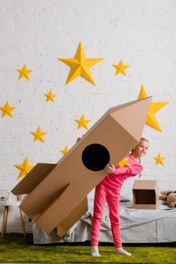 Full length view of excited kid holding big cardboard rocket in bedroom stock vector