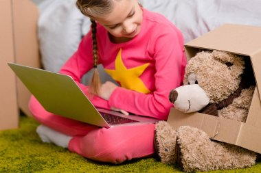 Cheerful kid with laptop sitting on carpet and looking at teddy bear stock vector
