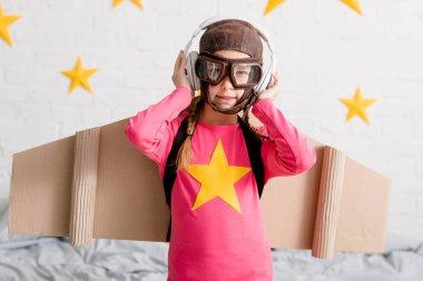 Kid in flight helmet and goggles listening music in headphones stock vector