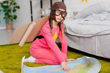 Cute kid in flight helmet sitting on carpet with map