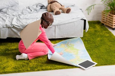 Child in pink clothes sitting on carpet and looking at map