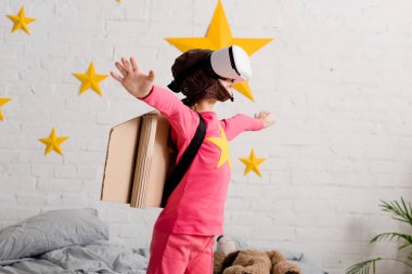 Kid in vr headset and pink clothes waving hands in bedroom