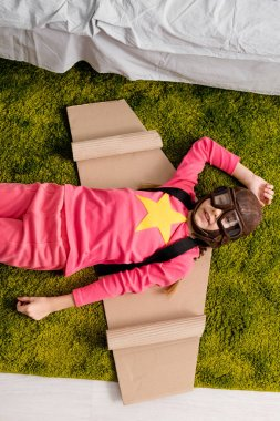 Top view of adorable kid with cardboard wings lying on green carpet stock vector