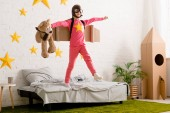 Photo Funny kid with teddy bear jumping on bed