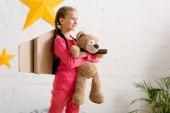 Boldog gyerek karton szárnyakkal rendelkező, teddy bear, és keres el