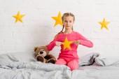 Dítě s copánky sedí na posteli a ukazoval prsty na žlutou hvězdou