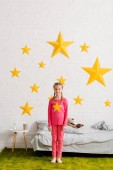 Cheerful kid in pink clothes standing in front of bed