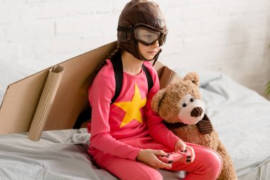 Child with teddy bear sitting on bed and holding joystick stock vector