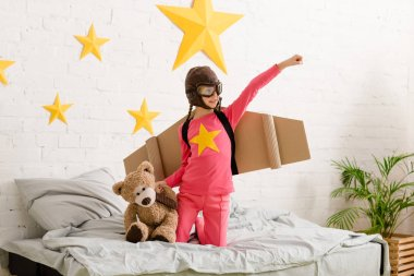 Smiling child with teddy bear standing on bed and holding hand up stock vector