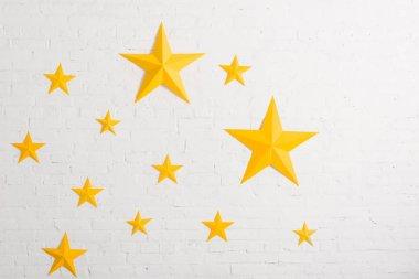 Yellow cardboard stars on light textured background stock vector