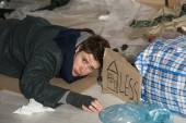 despaired homeless man lying on cardboard in rubbish dump, with symbol of house and less inscription on card