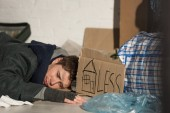 poor homeless man sleeping on rubbish damp with symbol of house and less lettering on piece of cardboard