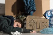 depressed homeless man lying on cardboard in rubbish dump, with symbol of house and less inscription on cardboard card