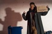 Fotografia uomo senza casa che tiene carta cartone con freegan lettering e mostrando il segno di vittoria