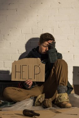 despaired homeless man sitting by brick wall and holding piece of cardboard with