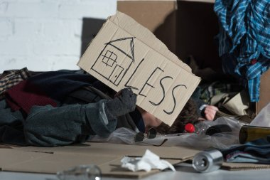 homeless man lying on rubbish damp with symbol of house and