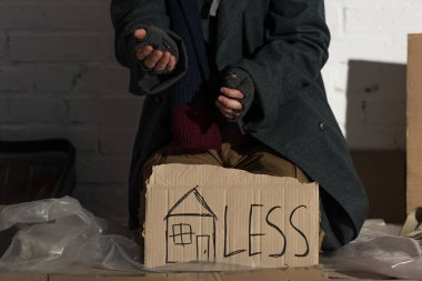 partial view of begging man with symbol of house and