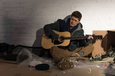 homeless man sitting on rubbish dump and playing guitar