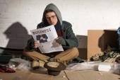 bezdomovec žebrák čtenářský deník podnikání zatímco sedí cihlová zeď