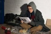 bezdomovec čtenářský deník podnikání zatímco sedí na skládce