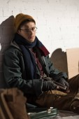Fotografie homeless man in glasses sitting on rubbish dump