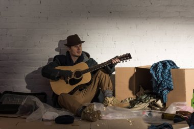homeless man sitting playing guitar while sitting on cardboard surrounded by rubbish