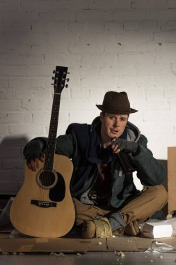 homeless man holding guitar while sitting on cardboard surrounded by rubbish