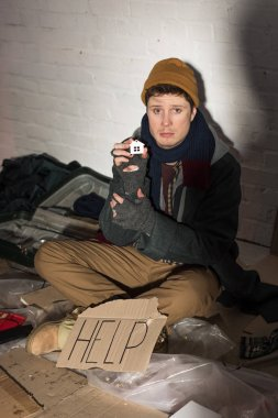 depressed homeless man sitting near cardboard card with