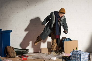 angry homeless man kicking cardboard box with garbage