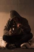 Junkie-Mann im dunklen Raum sitzen und Löffel mit Heroin auf leichtere Heizung
